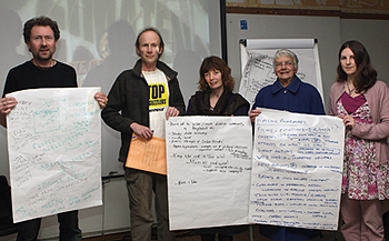 Participants hold up workshop action sheets